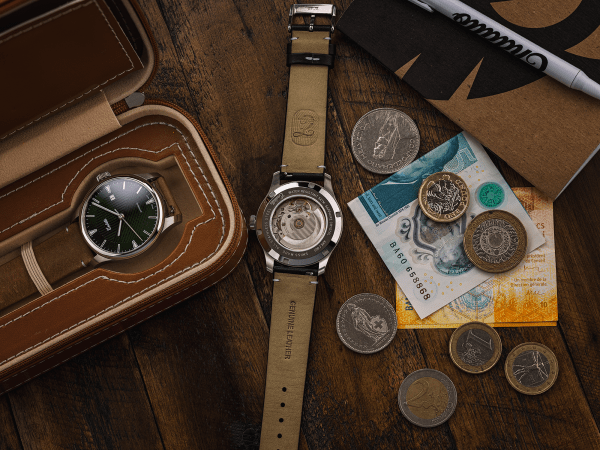 Exhibition caseback of a Swiss-made watch featuring a green dial and Eta 2824-2 automatic movement with a genuine leather strap set beside a travel watch case and currency