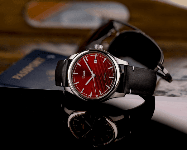 Swiss-made watch featuring a red dial and Eta 2824-2 automatic movement with a genuine leather strap set beside passport and sunglasses