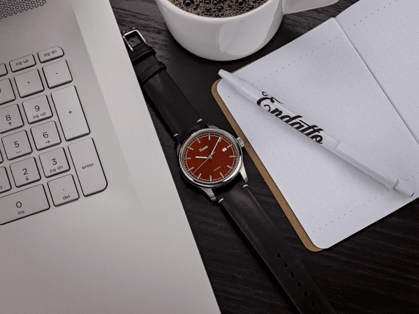 Swiss-made watch featuring a red dial and Eta 2824-2 automatic movement with a genuine leather strap beside a computer and coffee
