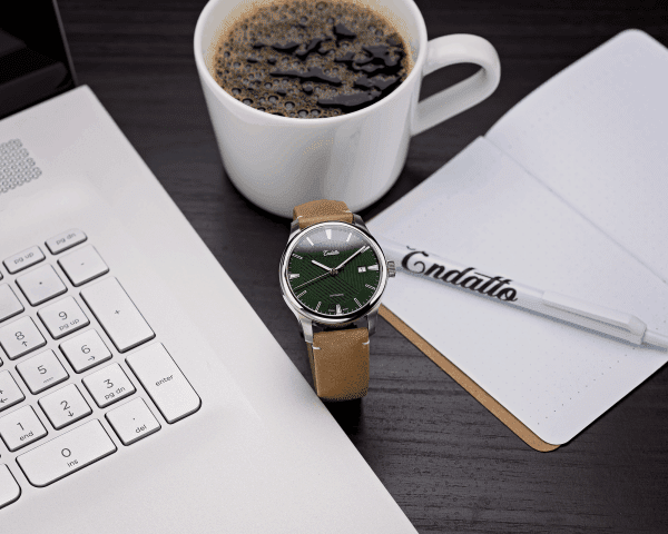 Swiss-made watch featuring a green dial and Eta 2824-2 automatic movement with a genuine leather strap beside a computer and coffee