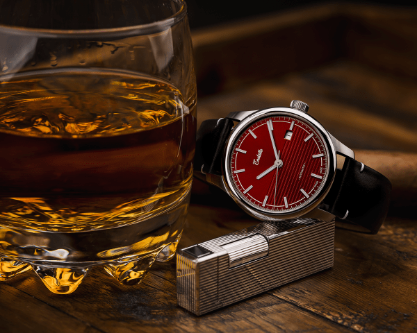 Swiss-made watch featuring a red dial and Eta 2824-2 automatic movement with a genuine leather strap beside whiskey and a cigar