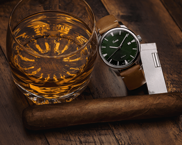 Swiss-made watch featuring a green dial and Eta 2824-2 automatic movement with a genuine leather strap beside whiskey and a cigar