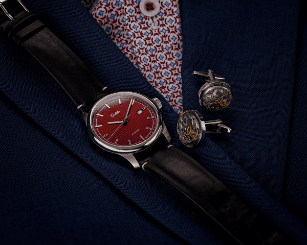 Swiss-made watch featuring a red dial and Eta 2824-2 automatic movement with a genuine leather strap set beside cuff links