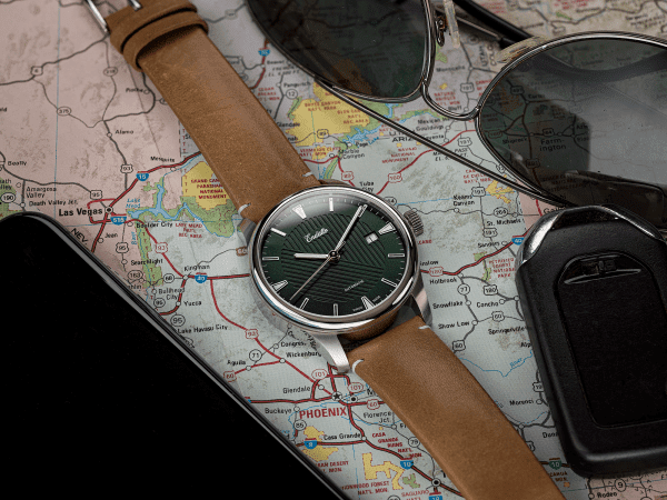 Swiss-made watch featuring a green dial and Eta 2824-2 automatic movement with a genuine leather strap set atop a map and beside sunglasses
