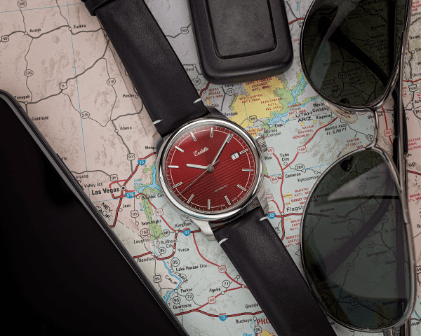 Swiss-made watch featuring a red dial and Eta 2824-2 automatic movement with a genuine leather strap set atop a map and beside sunglasses
