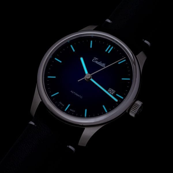 A swiss-made watch featuring an Eta 2824-2 automatic movement and a blue fume dial shown with lume.
